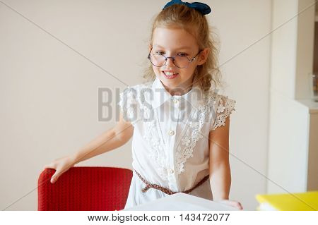 Cute little schoolgirl stands near desks. The girlie has a good mood. She smiles.