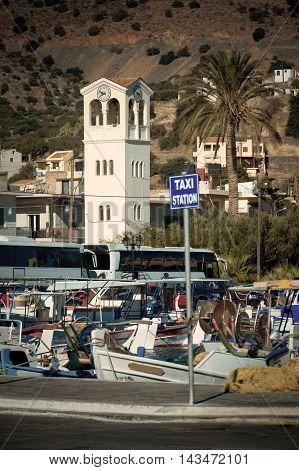 Pierce in Elounda. Coaches. Clock tower. The sign - Taxi. Crete Greece