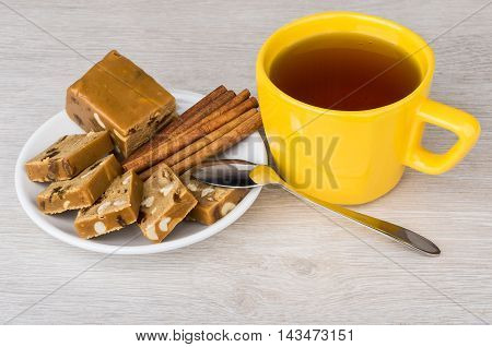 Pieces Of Sherbet In Saucer, Cup Of Tea, Cinnamon Sticks