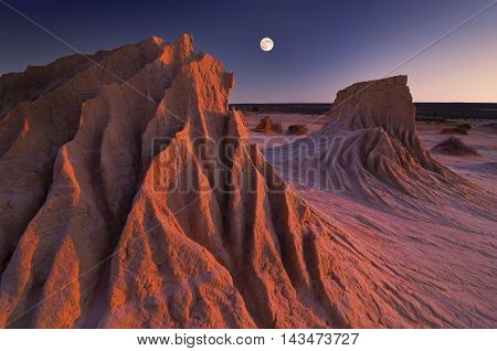 The full moon rises while the sun sets simultaneously at the ancient sandstone rock formations known as the Walls of China at Mungo National Park.