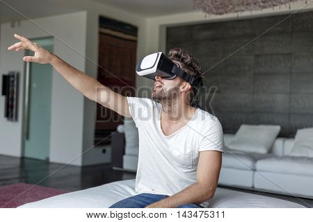 Casual caucasian man using VR headset at home
