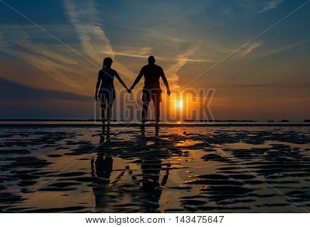 Couple hand in hand towards the sea in a dawn late summer in silhouettes