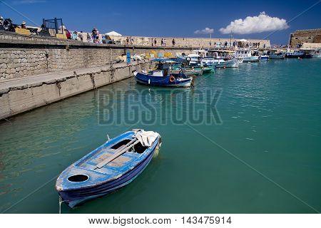 Heraklion CRETE ISLAND GREECE September. 21. 2013: Heraklion city's Old Port. Walk people. Fishing boats. Sunny day. Crete