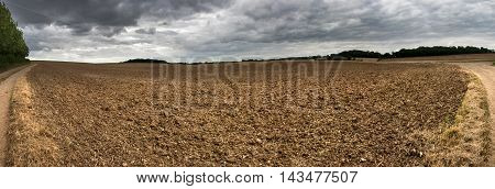 Freshly plowed field under the stormy dramatic sky.