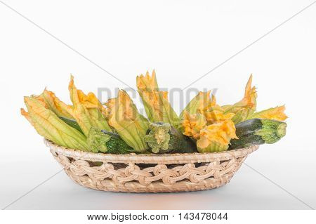 zucchini and zucchini flowers in a basket on a white background