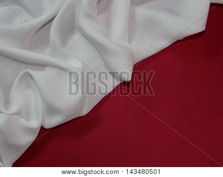 on a red silk lies white fabric, white fabric laid folds