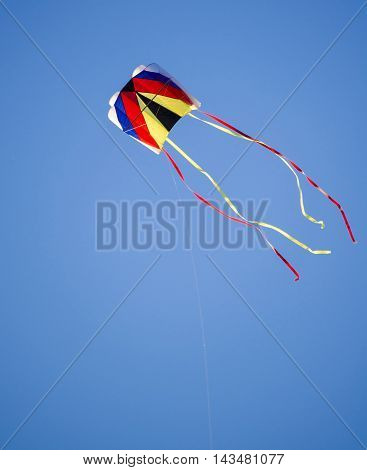 colorful kite flying high on blue sky