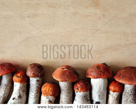 Fresh edible mushrooms with red caps and white trunks on a wooden surface. View from above. Background, place for text.