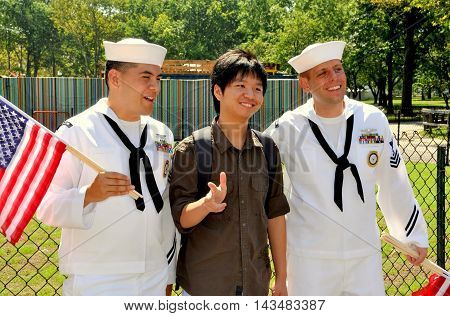 New York City - September 4 2009: Young man from Guangdong Province in China poses with two American sailors in Battery Park