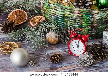Wicker basket with Christmas ornaments, spruce branch, watches, cones and dried slices of orange on old wooden table.