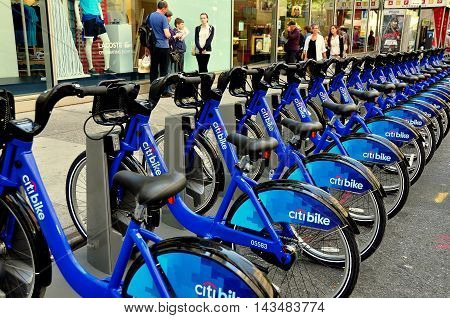 New York NY - May 27 2013: Rows of the brand new Citibike rental bright blue bicycles emblazoned with the Citibank logo sit at a West 49th Street docking station