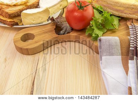 Plate and wooden platter with food - Tasty sandwiches white cheese and some vegetables on a wooden trencher and a plate.