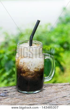 Iced black coffee with fresh milk in jug, jar, mug glass cups on the table