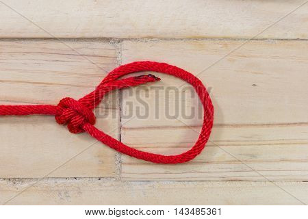 bowline knot made from red synthetic rope tightening on wooden background.