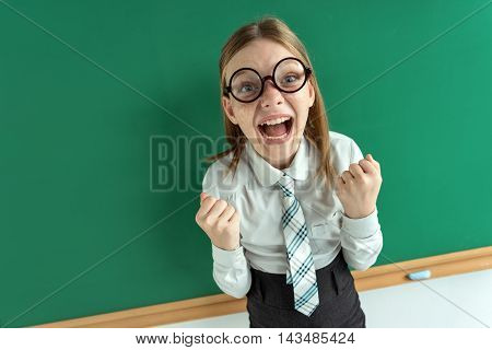 Humorous high angle view of Happy joyful laughing beautiful girl with hands on blackboard in classroom. Education concept