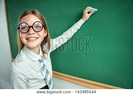 Young schoolgirl writing on blackboard. Photo of young teen creative concept with Back to school theme