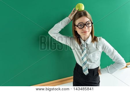 Young schoolgirl with an apple on her head. Photo of teen school girl wearing glasses near blackboard. Creative concept with Back to school theme