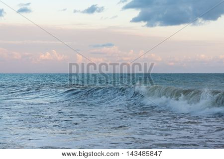 Sea waves against the cloudy sky in the evening before the storm