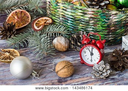 Wicker basket with Christmas ornaments, spruce branch, watches, cones and dried slices of orange on old wooden table.  Selective focus.