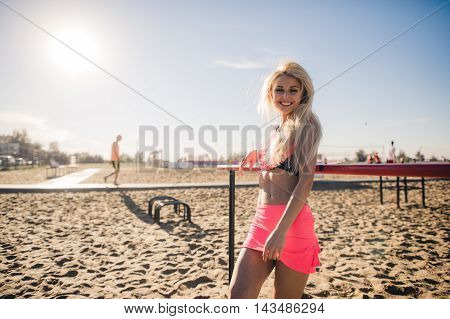 Portrait of a fit young woman resting after successful jogging workout outdoors. Pretty athlete blond wearing sportswear standing on beach during physical training.