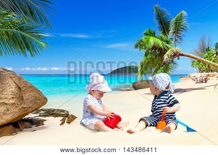 Baby twins playing on the tropical beach with blue lagoon