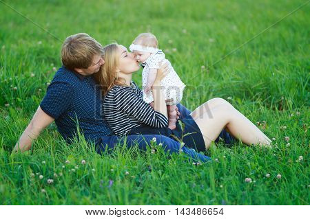 young parents with baby daughter outdoors. Family enjoys playing with baby in the park. Young beautiful mother kissing the tiny daughter. view profile. the concept of happy family
