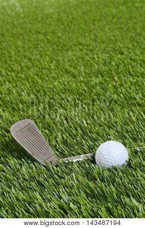 closeup of golf wedge club and ball on artificial grass