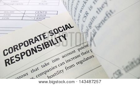 Corporate social responsibility word on the book with balance sheet as background