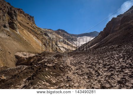 Walking into the crater of Mutnovsky Volcano on ash covered eternal snow, Kamchatka, Russia