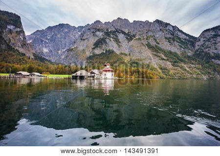 Dreamlike lake Konigssee. Red domes and white walls of the Church of St. Bartholomew reflected in the water. Picture taken from on board tourist boats. The concept of active tourism