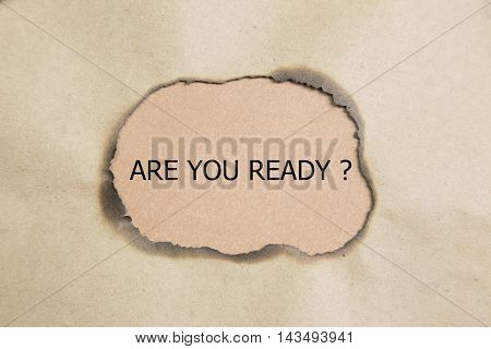 The question Are You Ready appearing behind torn brown paper
