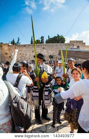 JERUSALEM, ISRAEL - OCTOBER 12, 2014:  Morning autumn Sukkot. The area in front of Western Wall of Temple filled with people. The Jews of ritual clothes - tallit hold four plants on Sukkot
