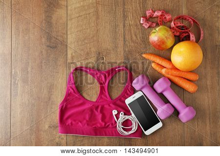 Sport equipment and clothes on wooden background, top view