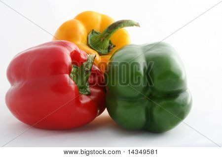 Three peppers on a white background - red, green and yellow