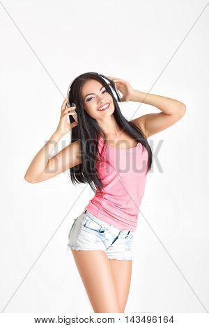 portrait of beautiful young woman with headphones listening to music. the girl enjoys the music