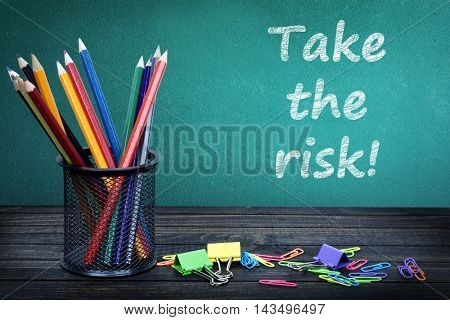 Take the risk text on green board and group of pencils