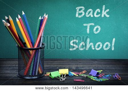 Back to school text on green board and group of pencils