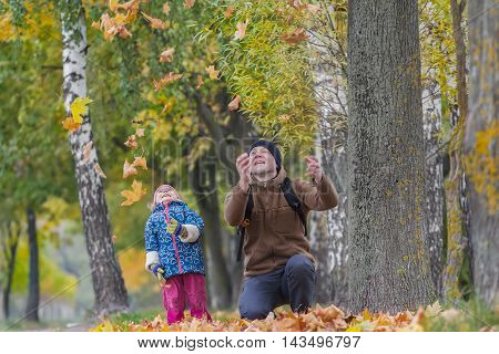 Smiling father with laughing daughter are tossing up yellow autumn leaves in park outdoors