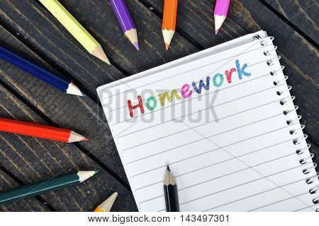 Homework text on notepad and colorful pencils