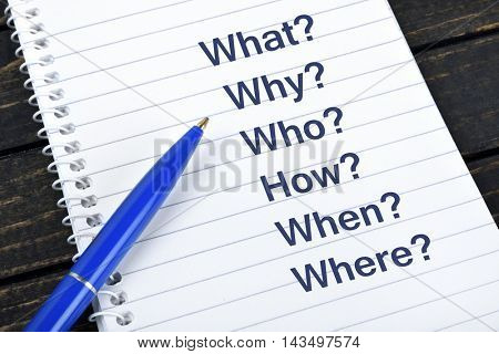 Questions text on notepad and blue pen