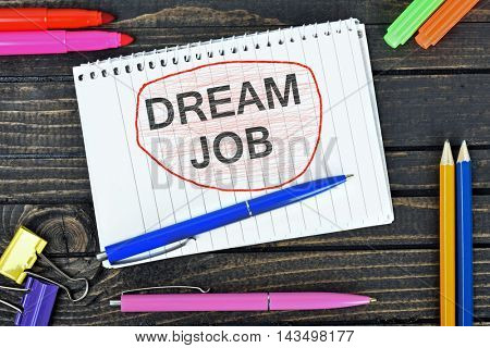 Dream job text on notepad and office tools on wooden table