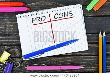 Pro and Cons text on notepad and office tools on wooden table