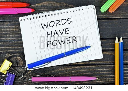 Words have power text on notepad and office tools on wooden table