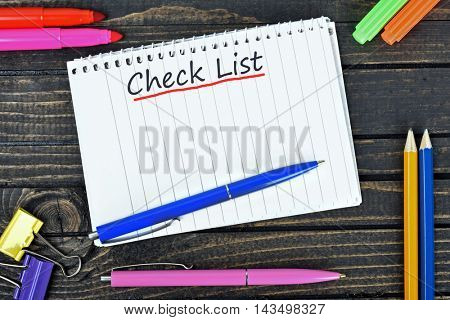 Check list text on notepad and office tools on wooden table