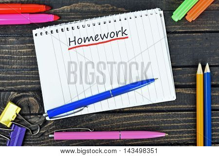 Homework text on notepad and office tools on wooden table