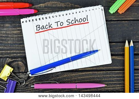 Back to school text on notepad and office tools on wooden table
