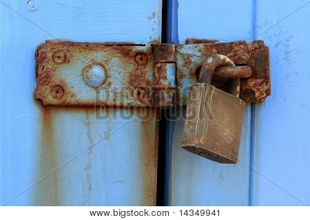 Rusted latch and padlock on weathered blue-painted doors.