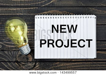New project text on notepad and light bulb