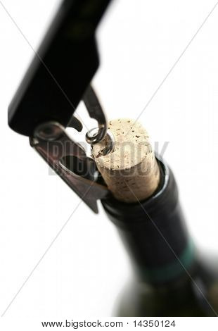 Closeup of a corkscrew pulling cork from bottle of white wine.  Shallow focus, white background.