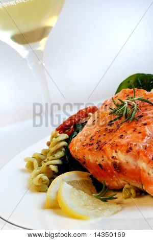 A grilled fillet of atlantic salmon, with fresh pasta salad and a glass of white wine.